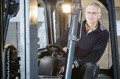 picture of forklift driver  - Experienced forklift driver is posing inside his forklift in a warehouse - JPG