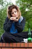 foto of rasta  - Rude rasta girl smoking and drinking beer on the wall - JPG