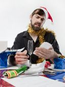image of christmas cards  - Man in Santa Claus hat loooking confused by the receipts from his Christmas spending - JPG