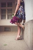stock photo of ombre  - Fashionable woman wearing a blue floral print dress gold shoes - JPG