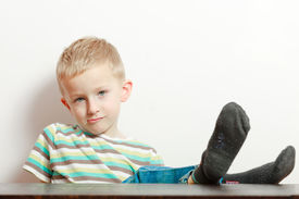 image of table manners  - Manners. Portrait of bored naughty boy child preschooler making sulky moody face. Kid with feet on the table