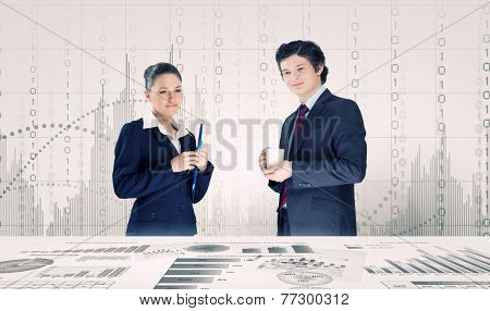 Young businessman and businesswoman discussing financial report