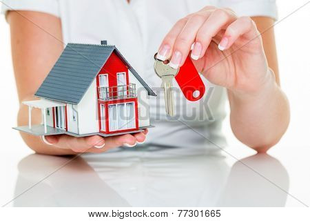 an agent for property with a house and a key. successful leasing and property for sale by real estate agents.