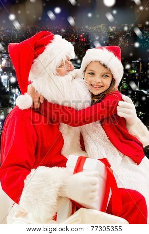 holidays, christmas, childhood and people concept - smiling little girl hugging with santa claus over snowy city background