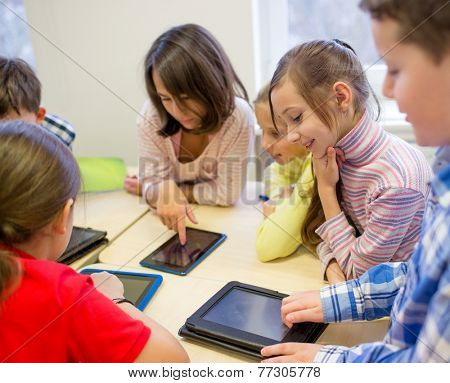 education, elementary school, learning, technology and people concept - group of school kids with tablet pc computer having fun on break in classroom