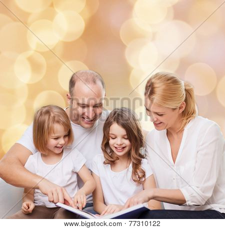 family, childhood, holidays and people - smiling mother, father and little girls reading book over beige lights background