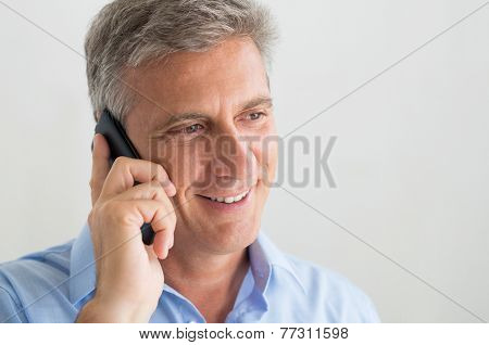 Closeup Of Happy Mature Businessman Listens On The Phone