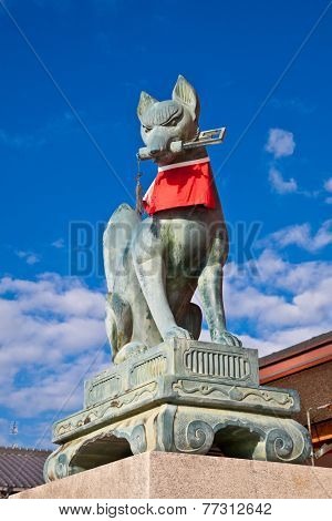 KYOTO, JAPAN-OCT 23, 2014: Fox holding a key in its mouth, at the main gate of the Fushimi Inari Shrine on Oct 23, 2014 in Kyoto, Japan. Almost all Inari shrines have at least a pair of these statues.