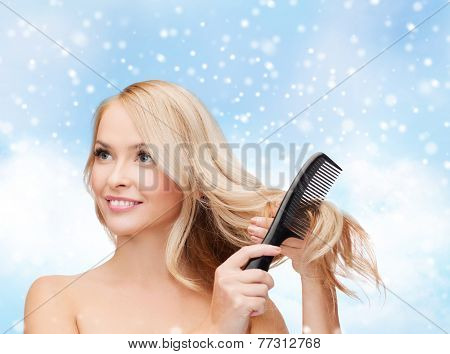 heath, people, haircare and beauty concept - beautiful young woman with bare shoulders combing her hair over blue sky, snow and clouds background