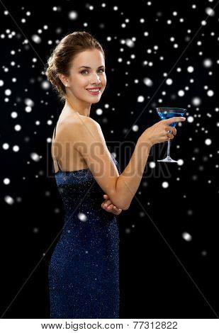 party, drinks, holidays, luxury and celebration concept - smiling woman in evening dress holding cocktail over black snowy background