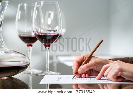 Female Hand Taking Notes At Red Wine Tasting.
