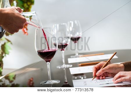 Hand Pouring Red Wine At Wine Tasting.