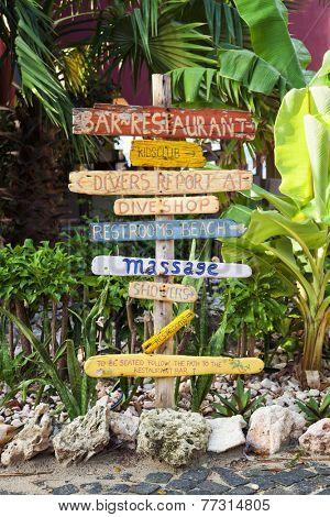 Signpost made of flotsam at tropical resort showing directions to facilities at beach