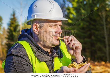 Lumberjack with potato chips in the forest