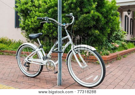 White Bicycle Locked To A Sign Post