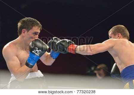 NOVOSIBIRSK, RUSSIA - NOVEMBER 29, 2014: Match Boris Georgiev (left) of Bulgaria vs Viacheslav Kislitsyn of Ukraine during AIBA Pro Boxing tournament. The winners will go to the