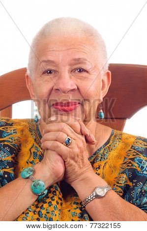 Elderly African American Woman sitting in a chair clasping hands and smiling