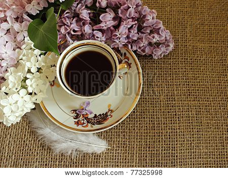 Cup Of Coffee And Lilac Flowers.