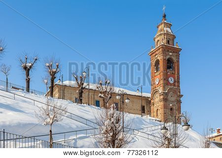 Parish church on the hill covered with snow under blue sky in small town in Piedmont, Northern Italy.