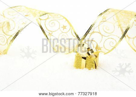 Golden Christmas Gift With Golden Ribbon On Snow