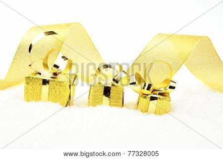Golden Christmas Gifts In Line With Ribbon On Snow