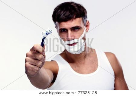 Portrait of young man shaving. Focus on shaver.