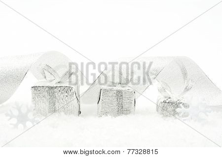 Silver Christmas Gifts With Silver Ribbon On Snow
