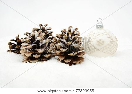 Single White Christmas Bauble With Pine Cones On Snow Isolated