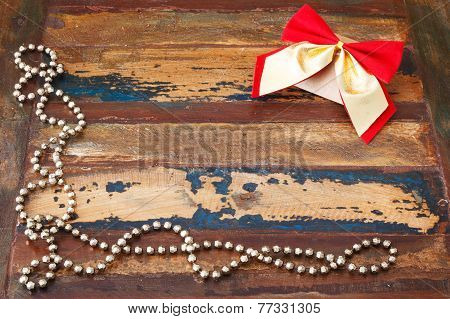 Background: Christmas Gift Package With Red Golden Bow And Chaplet