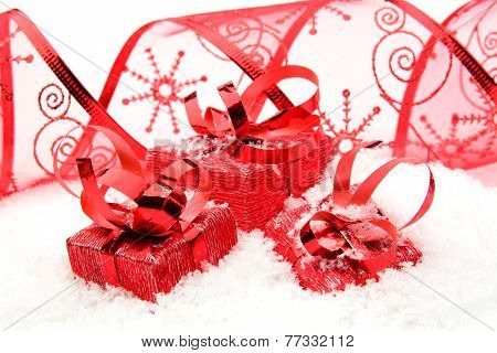 Three Red Christmas Gifts With Ribbon On Snow