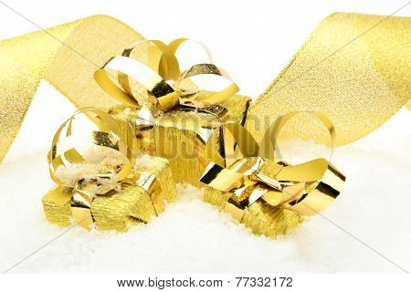 Three Golden Christmas Gifts With Ribbon On Snow
