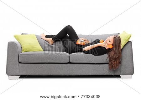 Girl lying on a sofa and talking on a vintage phone isolated on white background