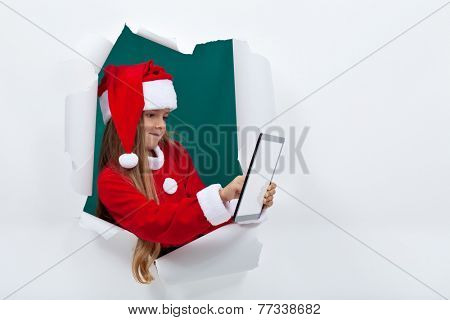 Little santa girl using tablet computer leaning through hole in white board - lots of copy space