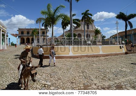 People and donkey in Plaza Mayor, in Trinidad de Cuba, Cuba, on a sunny day