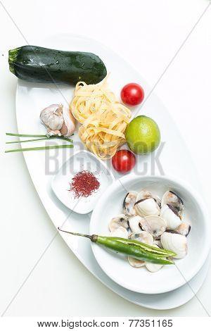 Garlic Cloves With Uncooked Pasta, Saffron, Scallops, Lime,  Zucchini, Cherry Tomatoes And Chilli Pe