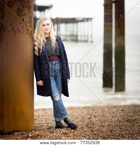 Blond Teenage Girl Leaning Against A Rusty Pier Support