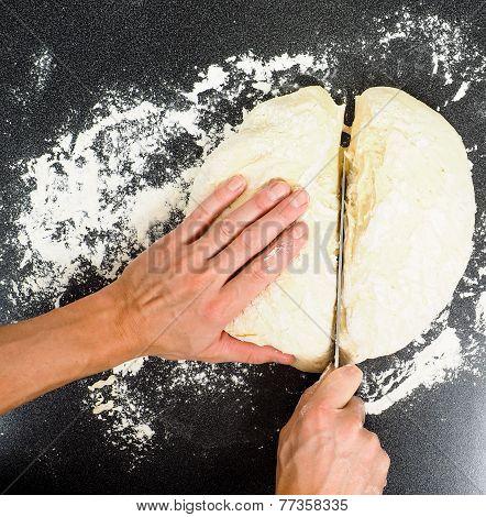 Hands Cutting A Lump Of Dough