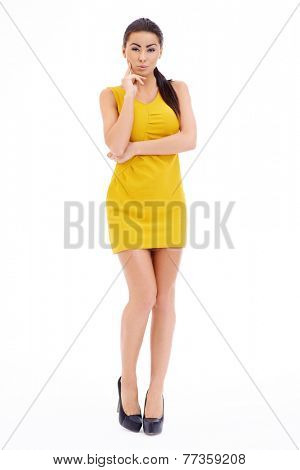 Full Length of Pretty Woman with Long Black Hair Wearing Sexy Yellow Dress with Arms Crossing the Body  Looking at the Camera. Isolated on White Background.