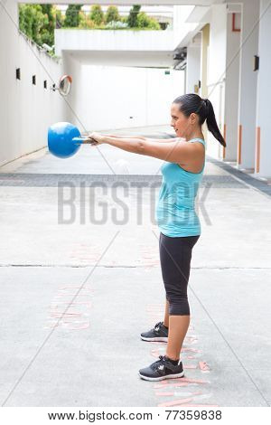 Beautiful hispanic sport woman swing the blue kettlebell, outdoor