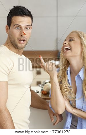Young couple having fun in kitchen, woman setting off ketchup on man's nose, laughing.
