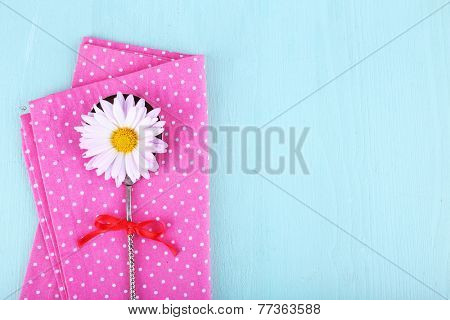 Camomile in metal spoon on pink polka dot napkin on wooden background