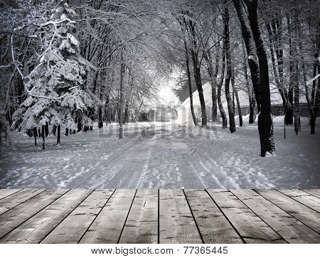 Winter park in the evening covered with snow with wooden floor