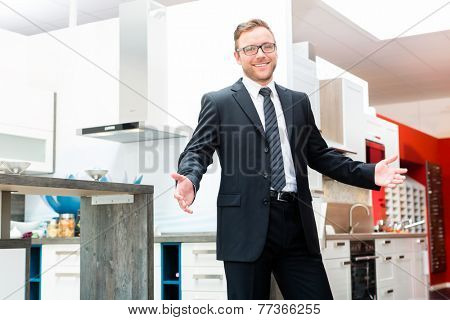 Salesman in domestic kitchen in studio or furniture showroom