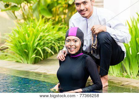 Muslim woman or girl in swimming pool in tropical garden wearing Burkini halal swimwear greeting her husband