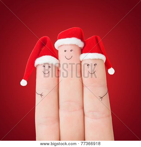 Fingers Faces In Santa Hats Against Red Background. Happy Family Concept For Christmas
