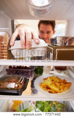 Man Looking Inside Fridge Filled With Food And Choosing Eggs