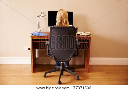 Woman Sitting At Desk Working At Computer In Home Office
