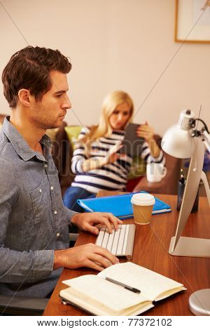 Man Sitting At Desk Working At Computer In Home Office