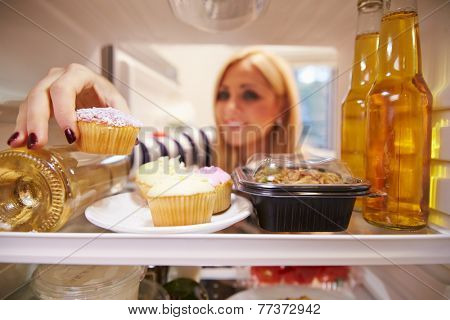 Woman Looking Inside Fridge Full Of Unhealthy Food