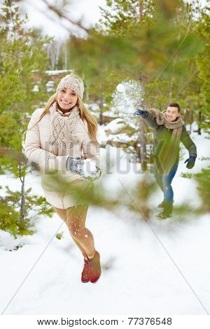 Happy girl and guy playing snowballs in winter park